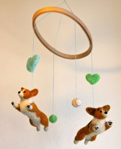 Pass on your love of Welsh Corgis to your new baby with this cheerful mobile. Two Corgis spin and jump, trying to catch the tennis and baseballs.