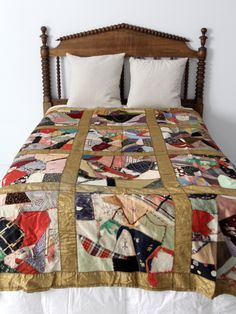 An antique crazy quilt blanket circa 1910. The patchwork quilt features multiple textiles with a gold satin border. There is an embroidered heart at the top. The backing is a soft gray cotton. - multi