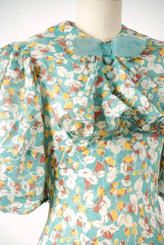 Vintage 1930s dress is fabulously styled, a NRA label dress that can be dated to 1933-35. The print is striking - warm in a way that makes one think of autumn, although the dress is perhaps better for spring and summer. The teal background is covered with white, mustard yellow and milk