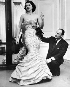Paris, March 1951: Janine Holland, 21-year-old 'Maid of Cotton, 1951' of Houston, Texas, is shown in a cotton evening gown designed especially for her by Pierre Balmain.  The American Cotton Queen is shown with Balmain during the final fitting. The gown is of Chartreuse cotton with burgundy colored roses covering one hip.