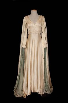 "Jeanette MacDonald ""Katherine"" Ecru medieval gown from Vagabond King. (Paramount, 1930) Ecru silk medieval gown with rabbit and ermine trim. Worn by Jeanette MacDonald as ""Katherine"" in the scene where she thanks Dennis King for ordering out the enemy in Vagabond King. No label. Exhibits stains on the front of gown, fur is worn and missing in places, collar and bodice beading added later."