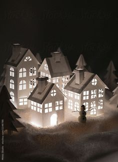Snowman and shining houses in winter forest