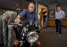 A Triumph Thruxton ACE Special Edition is on display in the offices of ACE Cafe North America in Overland Park. The company is led by (from left) CEO Mark McKee, chief marketing officer Steve Glum and chief financial officer Eric Forward.