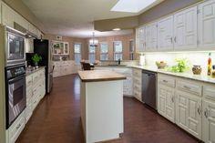 White cabinetry, butcher block island, and granite countertops