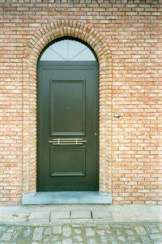 Voordeur in aluminium met inlegpaneel Camargue. De deur is voorzien van een horizontale siertrekker. Boven de deur zit een vast bovenlicht met kruishouten in het glas.