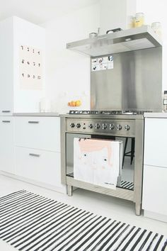 ♥b&w kitchen with striped rug and stainless range