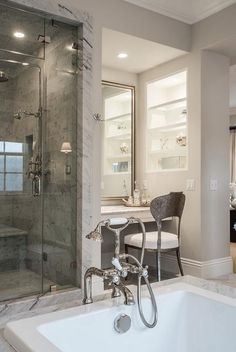 Chic bathroom features a shower clad in grey marble next to a nook filled with a floating make up vanity paired with an Oly Studio Beverly Side Chair and a silver leaf mirror next to a lighted niche filled with shelves.