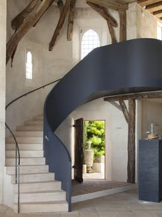 the style saloniste: Time Travel: A Brilliant Design Invention, love the dark modern stair paired with the rustic beams and soft plastered walls
