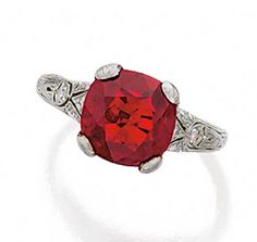 RUBY AND DIAMOND RING, CIRCA 1920.  The cushion-shaped ruby weighing 5.09 carats, the pierced shoulders set with single-cut diamonds, mounted in platinum