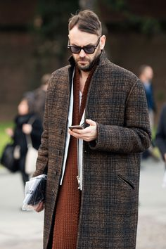 Pairing a brown tartan overcoat with a white leather biker jacket is an on-point option for a day in the office.  Shop this look for $591:  http://lookastic.com/men/looks/dark-brown-sunglasses-tobacco-scarf-brown-overcoat-white-biker-jacket/7775  — Dark Brown Sunglasses  — Tobacco Knit Scarf  — Brown Plaid Overcoat  — White Leather Biker Jacket