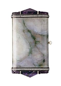 AN ART DECO JADE, AMETHYST AND DIAMOND VANITY CASE, BY VAN CLEEF & ARPELS The rounded rectangular jade case, with black enamel and rose-cut diamond borders, the terminal set with a pyramid-shaped carved amethyst foliate plaque, the pearl pushpiece opening to reveal a fitted mirror and powder compartment, circa 1930, 3¾ x 2 x 5/8 ins., with French assay mark and maker's mark Signed Van Cleef & Arpels, Paris, no. 31206
