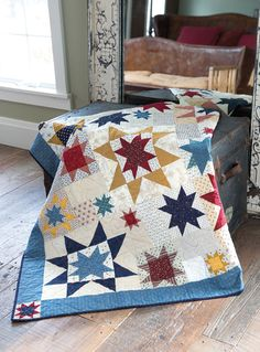 """Liz Porter's Quilt of Valor definitely has star power. She used combinations of 4"""", 8"""", 12"""", and 16"""" stars in a classic red, blue, and gold color scheme. This quilt is featured in the Fons & Porter's Love of Quilting 2600 TV series."""