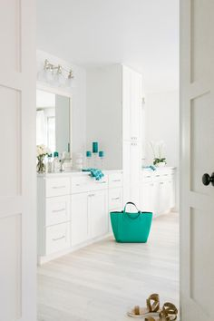 A walk-in closet accesses the bathroom. A dark teal color was used for the accessories in the room to add pops of bold tones.