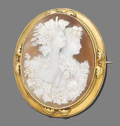 A mid 19th century shell cameo brooch/pendant  The finely carved oval cameo depicting Bacchus and Ariadne in profile, within a collet-setting applied with textured vine-leaf and ropetwist decoration, length 7.2cm.