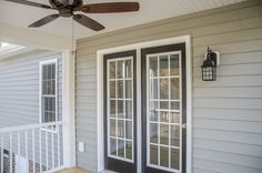 Screened porch off the back of this custom home with French doors and an outdoor ceiling fan ©Balducci Builders