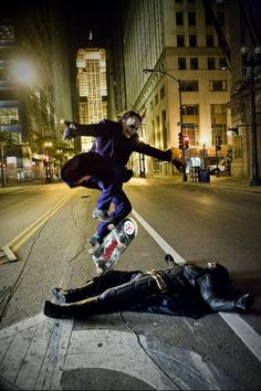 Heath Ledger as The Joker skateboarding over Christian Bale as The Batman.
