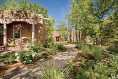 Santa Fe, adobe compound rife with aspens, desert grasses and flowering plants. The guesthouse, foreground, was once a Franciscan chapel and is thought to be at least 200 years old.