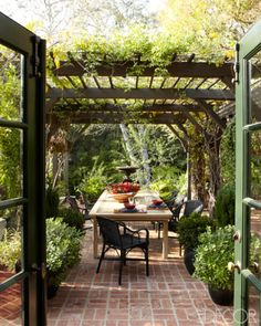 Chairs from Maison Midi surround an elm dining table beneath the pergola at a Hollywood home.