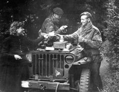 """Pausing for a moment on their push to Arnhem, (Market-Garden, Sep. 1944) two British soldiers enjoy an impromptu picnic provided by a grateful Dutch girl. - British leaders found that the crowds of joyous civilians made it very difficult for their troops """"to keep alive to the possibility of a German attack."""""""