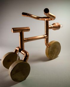 Copper Tricycle, exposed bulb, table lamp!    This funny lamp will make everyone remember childhood and bring a smile to their face. Ideal gift for collectors of unusual things.    We took extra care in all details while assembling this copper lamp:   The body is assembled from copper pipes (coated with protective layer). The wheels are made from wooden disks (treated with natural wax).  Light bulb socket is ceramic type, for extra safety.    For best results we recommend very low power…