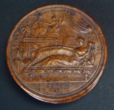 Circular French pressed wood snuff box, c.1810. The lid has a lovely neo-classical design of a woman reclining on a couch, playing the harp, with drapery, urns and statuary in the background. There is a French motto on both the upper and lower portions of the lid.