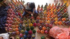 - Artista indiano decora potes de óleo em sua casa, na periferia de Hyderabad. Eles serão usados como lanternas durante as festividades. Foto: Noah Seelam / AFP