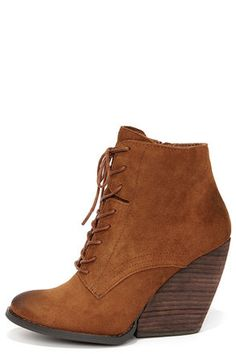 "The other booties in your life will have a hard time competing against the standout style of the Very Volatile Arlington Tan Suede Leather Lace-Up Wedge Booties! Soft genuine kid suede in a rich tan covers an almond toe upper, sweeping up into a lace-up vamp (with round laces) and ending at an ankle-high collar. A matching 6"" zipper at the instep makes this boot easy to slip on, while the 4"" stacked wedge heel (including tip) adds a girly touch to this cool boot. Oil rubbed accents on the…"