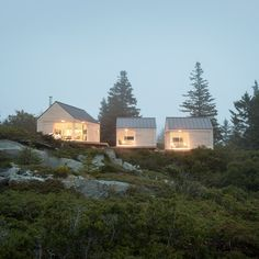 US design-and-build firm Go Logic has completed a summer house on the rocky coastline of Maine made up of three wooden cabins, each linked by terraced decks