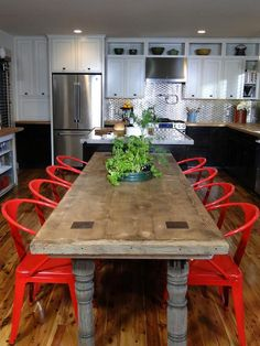Reclaimed Wood + Ruby-Red Metal  Farmhouse meets industrial in this wonderful table and chair combo. Colors and materials are also blended throughout the rest of the kitchen to create an inviting atmosphere.