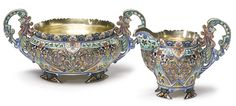 A Russian gilded silver and cloisonné enamel part tea set, 11th Artel, Moscow, 1908-1917, in the cockerel style, comprising a cake basket and creamer enameled with polychrome stylized foliate and geometric ornament with stippled gilt reserves, the pierced handles shaped as stylized birds, raised on bracket feet.