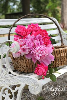 basket of pink peonies and roses on white garden bench
