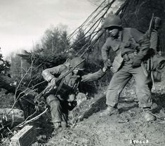 Hurtgen-gallery-2 Private First Class Benny Barrow of Company I, in the 4th Infantry Division's 8th Regiment, helps his buddy up a ragged Hürtgen Forest hill.