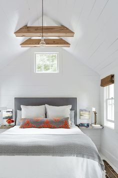 "Use architectural interest €""like in this master bedroom where, wood beams draw the eye up. This handsome duo was crafted using leftover pine from the floors."