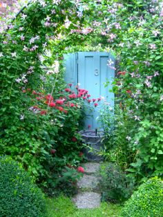 A door to nowhere - but it sure makes an attention-getting, colorful backdrop - via ArtofGardening