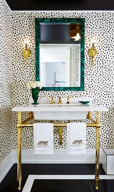 black and white wallpaper, gold sconces, malachite mirror, green mirror, gold faucet, white and gold console sink