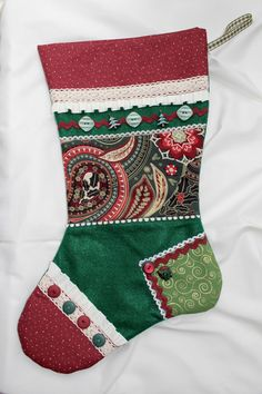 This hand crafted holiday stocking will look stunning on your mantle just in time for Santa's arrival.  Notice the details of coordinating fabrics, edgings, trims and laces. The base of the stocking is felt with plain felt on the back. It is lined inside with a beautifully coordinating fabric and a special interfacing to add stability. A ribbon hanger is attached.