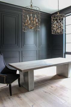black millwork dramatic dining room concrete table modern aged french oak wood floor