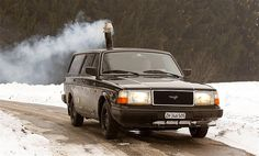 Smoke from a wood stove comes out of a chimney as Pascal Prokop drives his 1990 Volvo 240 station wagon during cold winter weather on a road near Zurich.