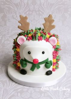 Hedgehog cake with colourful buttercream flowers dressed as rudolph the red nose reindeer! See link for my hedgehog cake tutorial