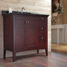 A tobacco brown wood stain adds refined style to this 42-inch bathroom vanity, featuring a rustic black granite single sink top. Two soft-close textured doors and three drawers provide plentiful storage space for a variety of personal items.