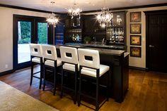 Black cabinets. Bar stools bring brightness to the basement bar [Design: Tavan Group]