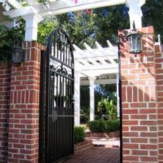red brick columns supporting white trellis canopy over back porch with black wrought iron gate and lighting