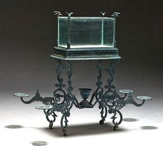 Ponds in the Parlor – Antique Aquariums ANTIQUE CAST IRON AQUARIUM Victorian cast iron aquarium with flower stand, possibly Adams Brothers Foundries. With bird finials at box corners, central urn centered on base, and four detachable swing arms for flower pots. Measures 51″ high x 26″ wide (58″ wide, with arms attached) x 16″ deep. Sold at Cowan Auctions. [Image credit: Cowan Auctions]