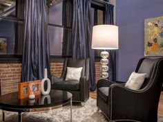 Chic black leather armchairs carve out a relaxing sitting area in this master bedroom. Metallic blue curtains lend a sense of luxury to the contemporary space.