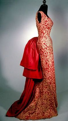 "1959, Balenciaga ""Eisa"" Dress of red taffeta with slim silhouette and satin bustle."