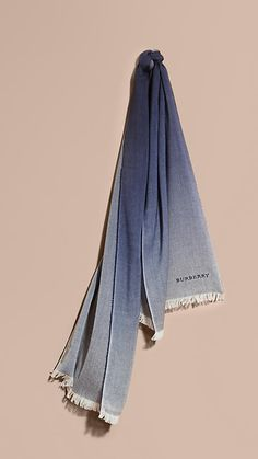 A scarf in a wool-cashmere blend woven for lightness and year-round wearability at a Scottish mill. The deep ombré design is framed by eyelash fringing at both ends.