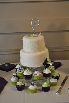 A simply elegant cream fondant covered two tiered cake. The top layer had dots, the bottom just a plain band around the bottom. The simple cake was set off with 225 purple flowered & lime green flowered cupcakes.