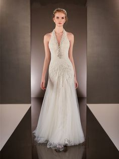 This heirloom quality Lace and Tulle over Parisian Silk Chiffon sheath bridal gown with a V-neckline features elegant Diamante beading on the halter. The slim Tulle skirt flows freely into a chapel train while the dramatic low back has a zipper closure.