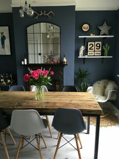bleu cyan salle à manger ouverte avec grande cheminée noire classique et des chaises en plastique autour de la table en gris foncé et en gris clair