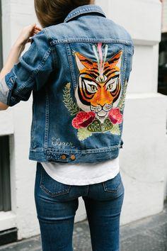 chaqueta de tela de jeans y en la espalda un dibujo de un leon
